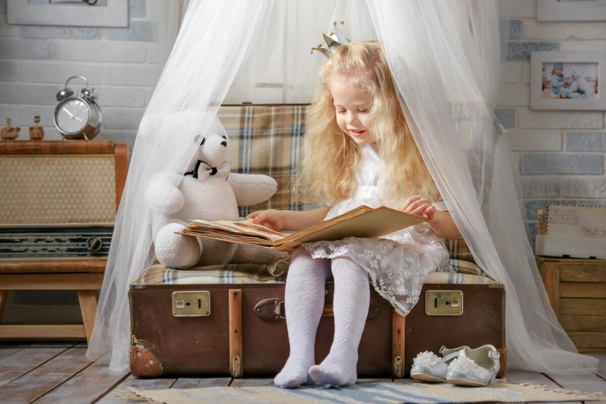 Little girl dressed as a princess plays in the room in the attic.