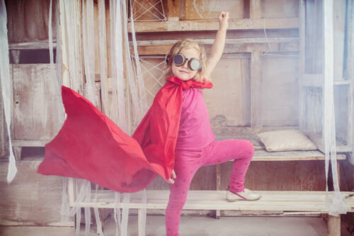Little child girl plays superhero. Girl power concept