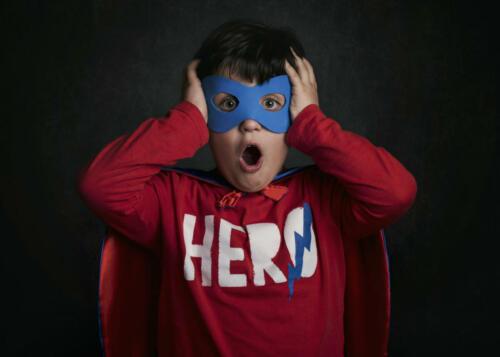 superhero. niño sorprendido disfrazado de superheroe