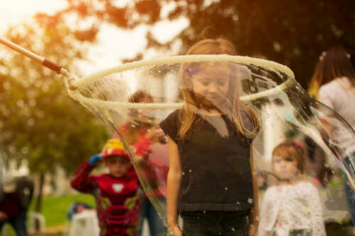 Baby girl stands in a huge soap bubble on, a holiday fun for children