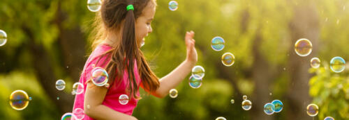 Curly girl catch a soap bubbles. Happy childhood concept.